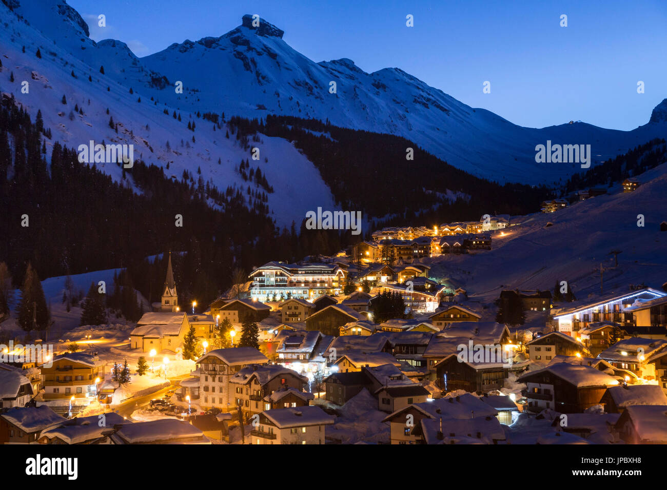 Lights of dusk on the alpine village of Arabba framed by snowy peaks Dolomites Belluno province Veneto Italy Europe - Stock Image