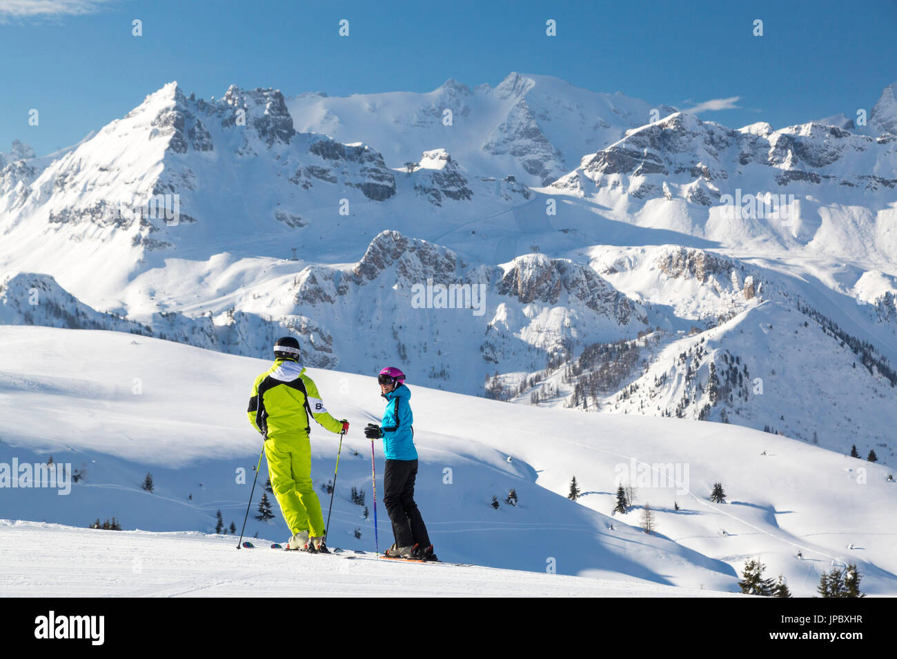 Skiers on ski slopes of Cherz framed by the high peaks of Marmolada and Portavescovo Arabba Dolomites Belluno Veneto Italy Europe - Stock Image