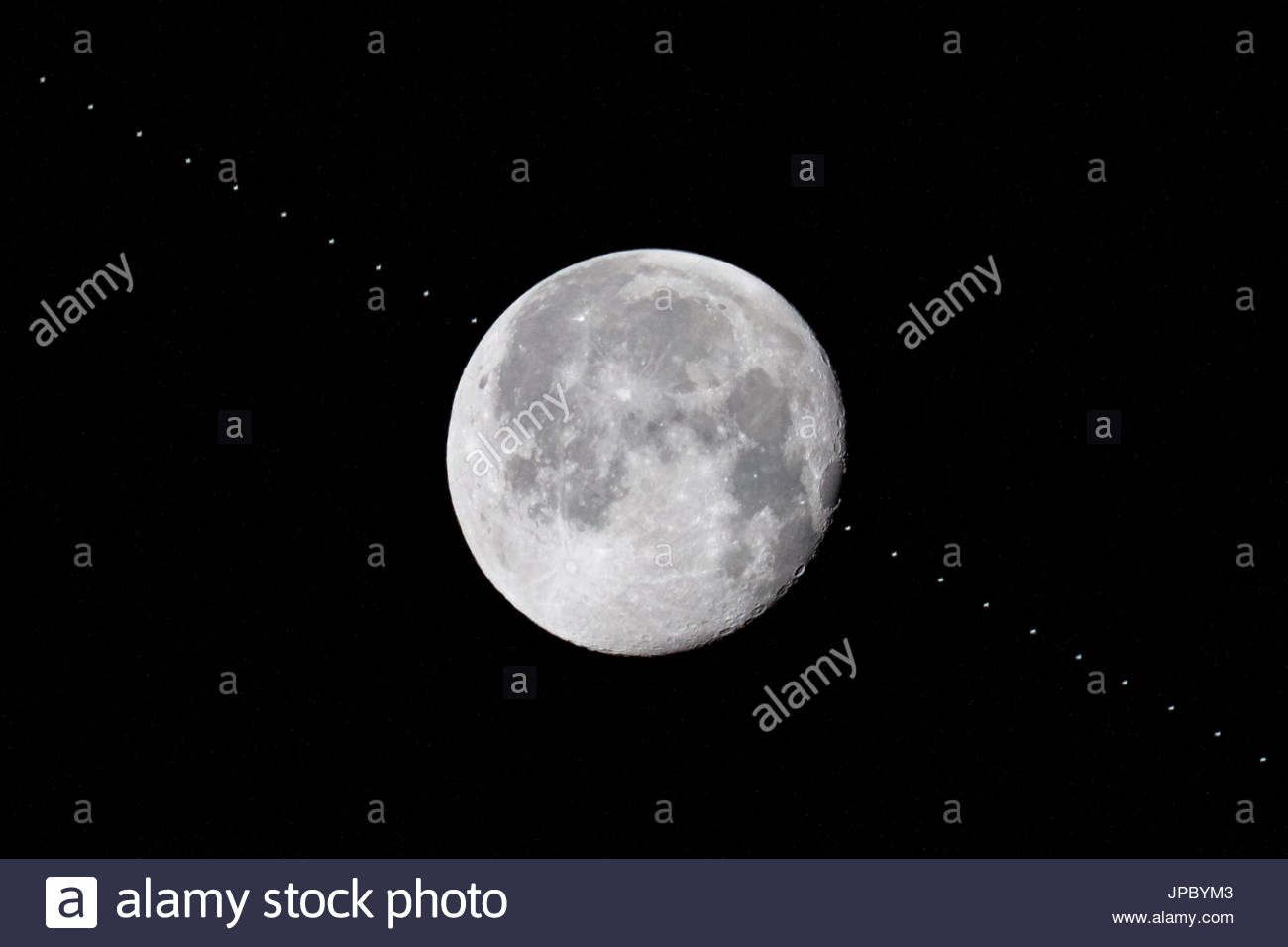 ISS International Space Station passing in front of full moon, multi-exposure image, various stages of fly-by progress, satellite orbit flight path - Stock Image