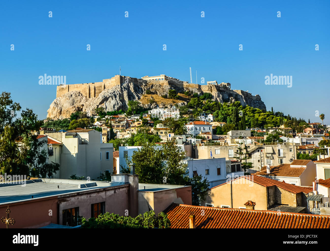 The ancient Parthenon on Acropolis Hill in Athens Greece taken from the rooftop of a city building on a hot summer day - Stock Image