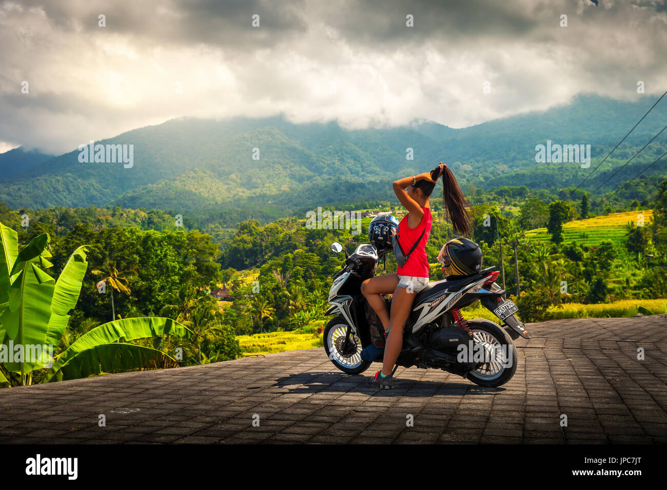 Young travel girl tourist explore tropical island Bali by bike and enjoy breathtaking view nature mountain landscape in foggy clouds. Travel concept - Stock Image