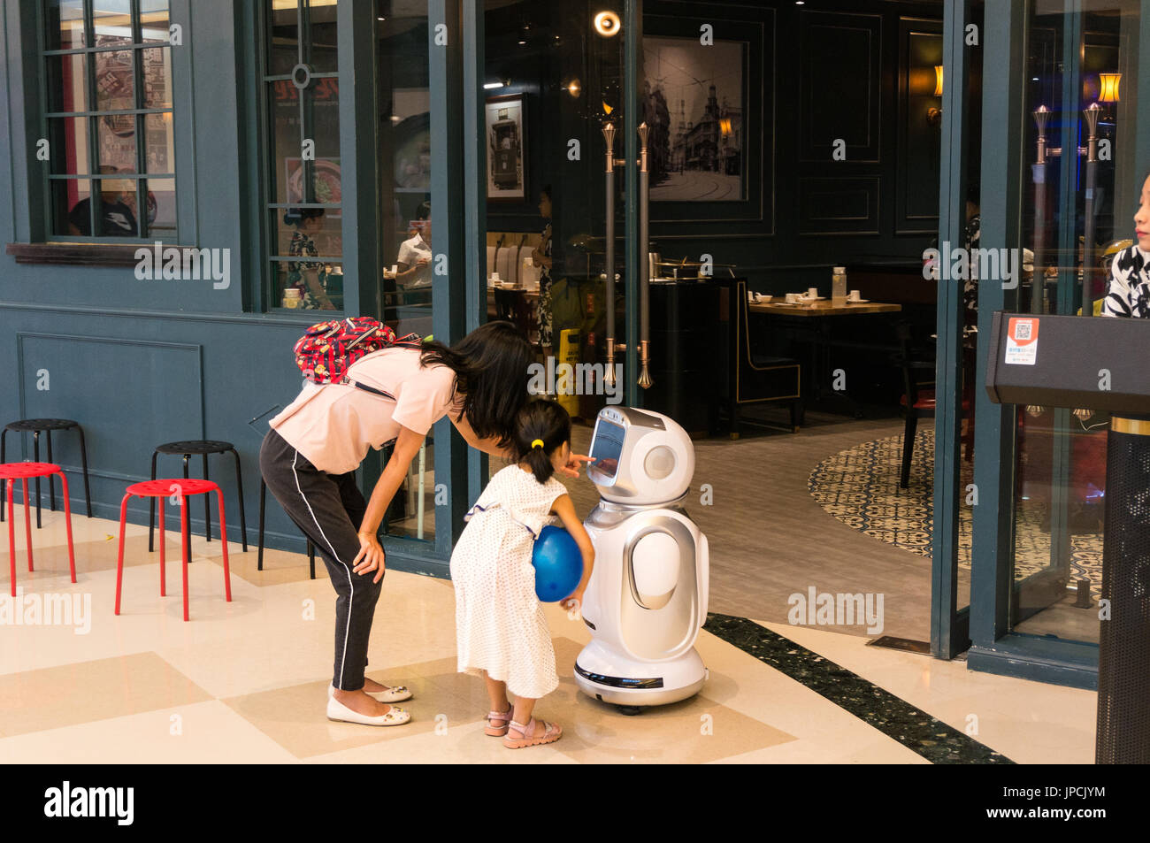 Mother and young girl interacting with restaurant robot in Shenzhen, China - Stock Image