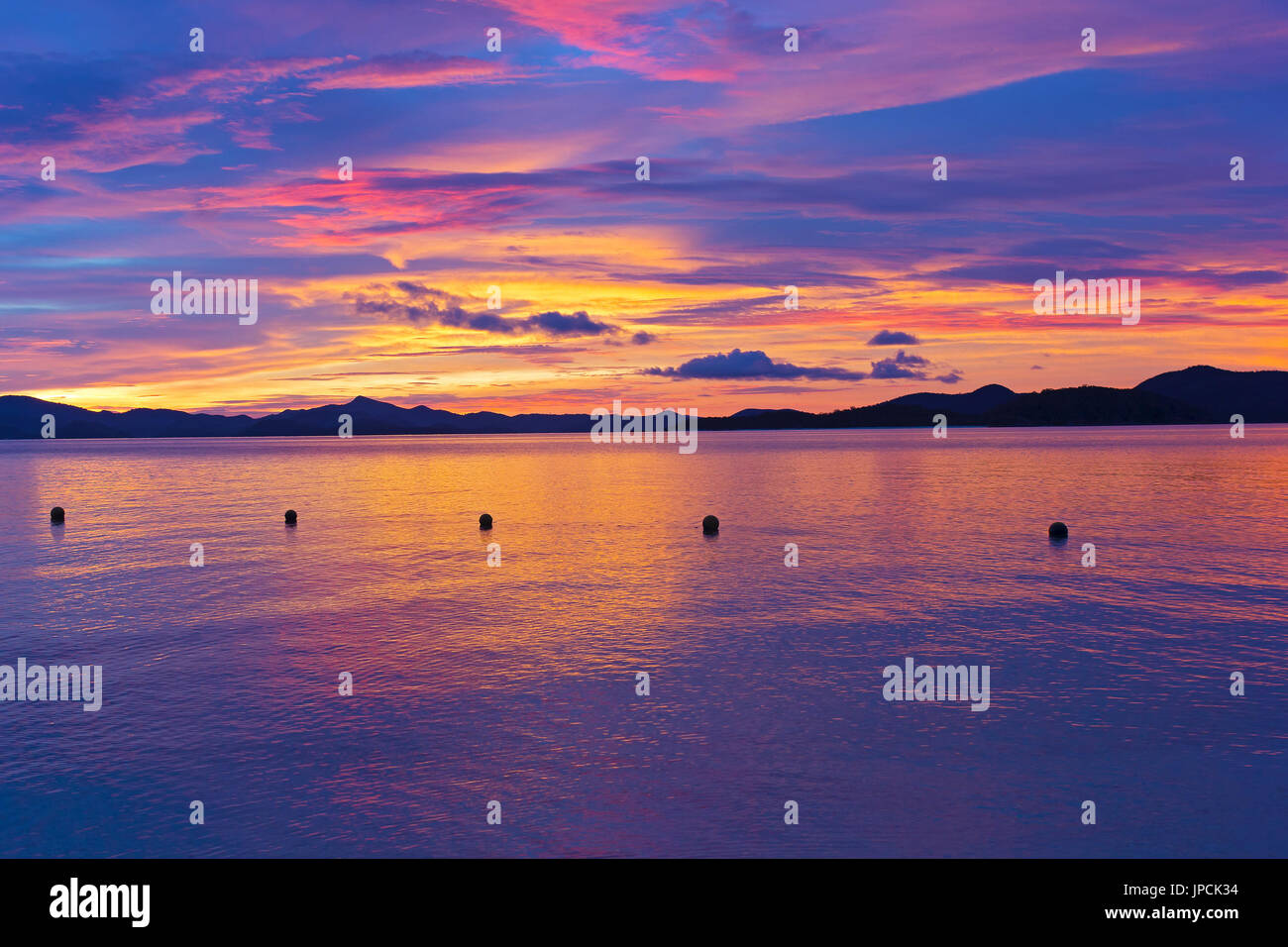 Unearthly sunset colors on a tropical island. Ocean landscape with mountain ridges on the horizon at sunset. - Stock Image