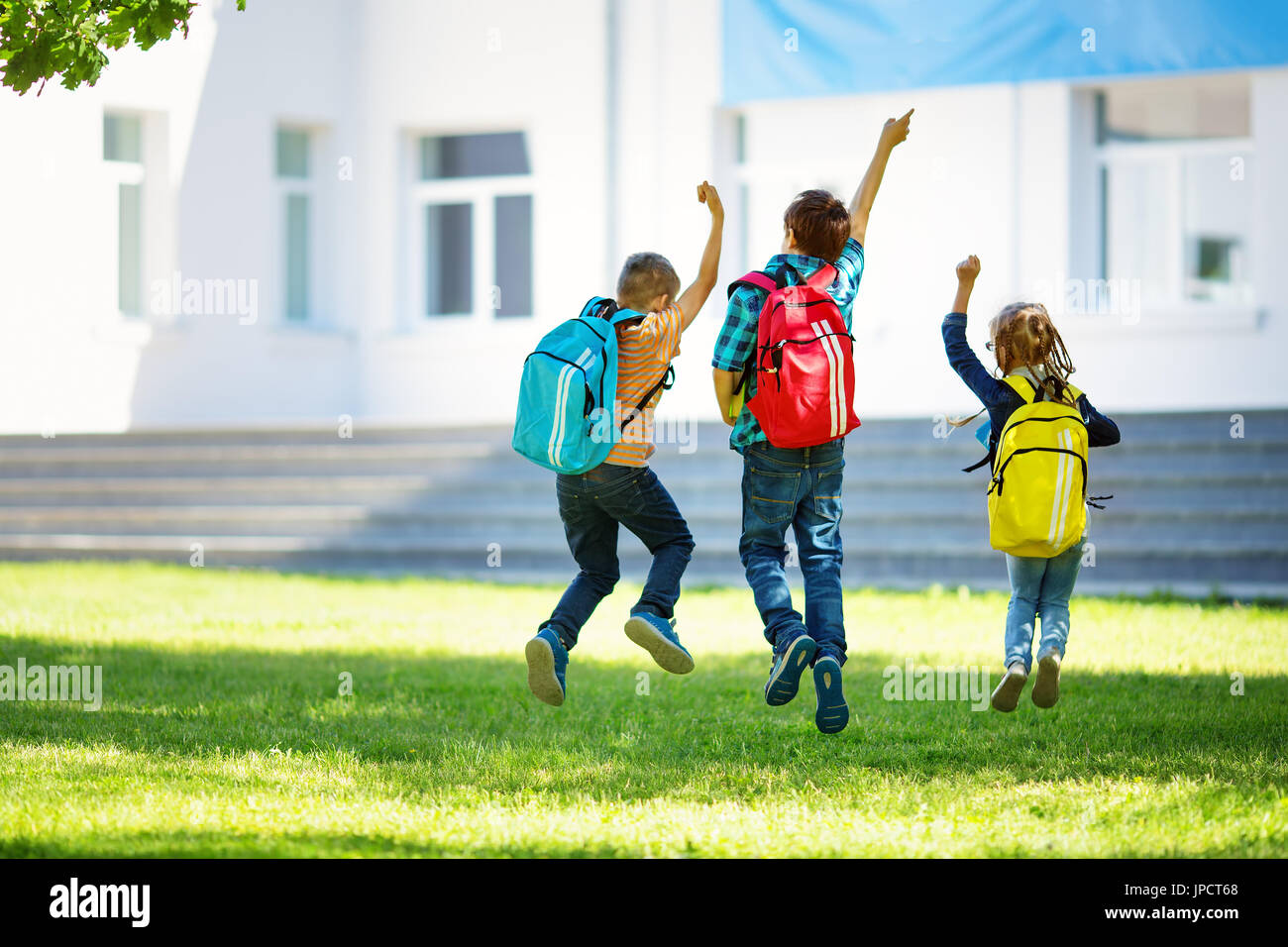 Children with rucksacks jumping in the park near school. Pupils with books and backpacks outdoors - Stock Image