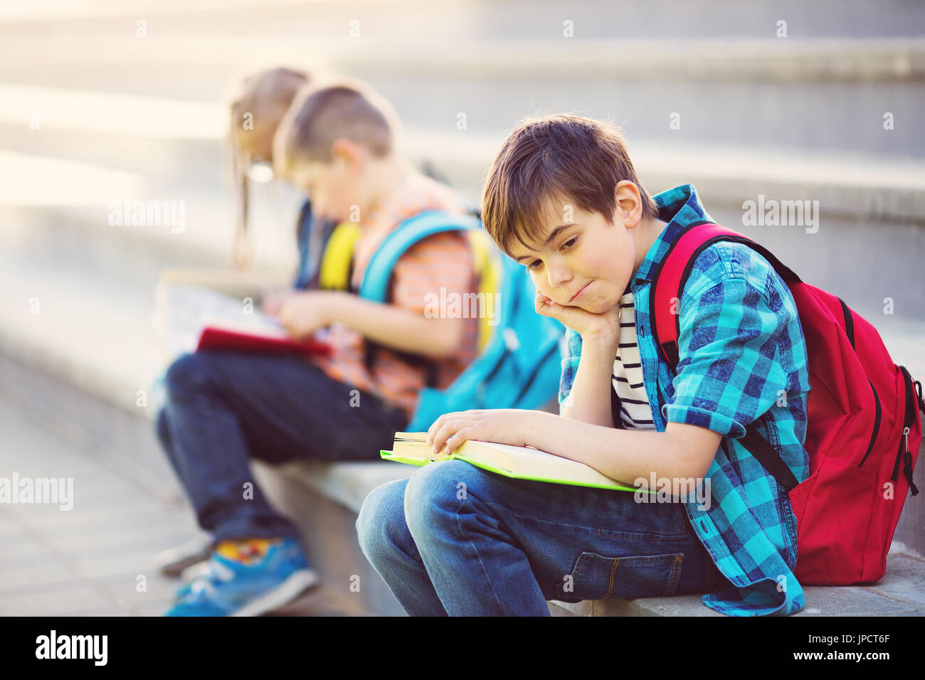 Children with rucksacks sitting on the stairs near school - Stock Image