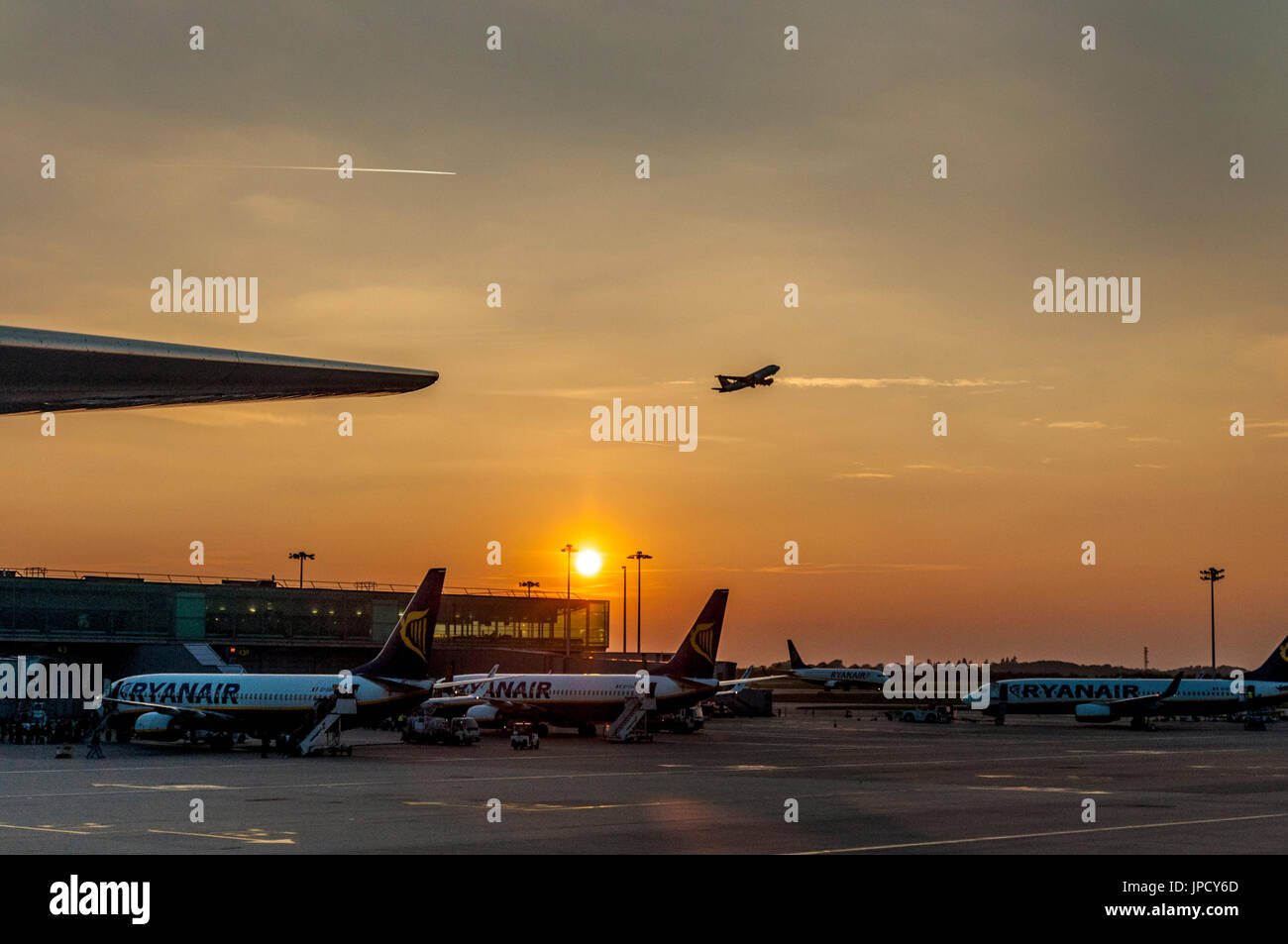 London Stansted Airport aircraft taking off at sunset. - Stock Image