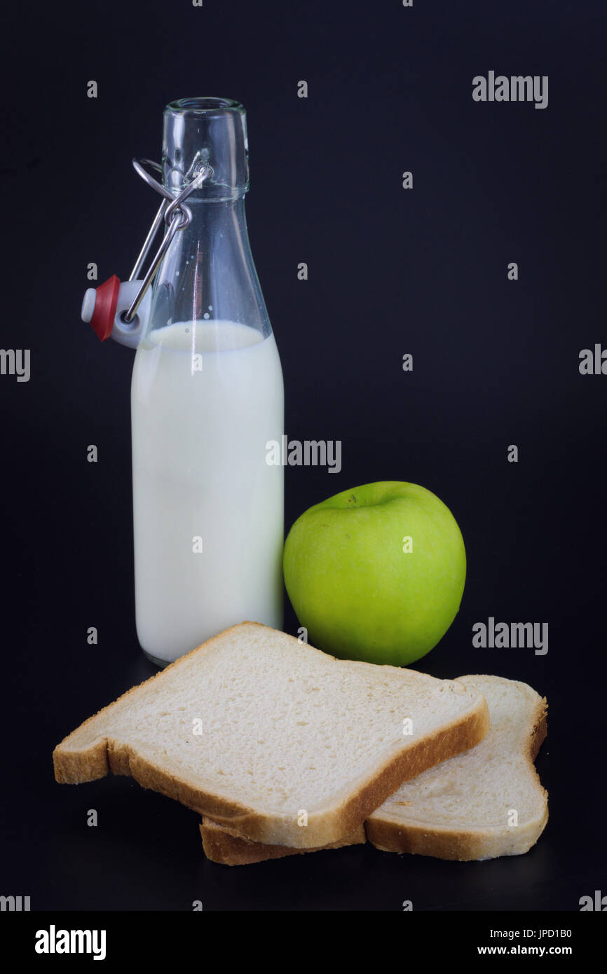 Energy breakfast for diet Bread, milk and green apple on black background Stock Photo