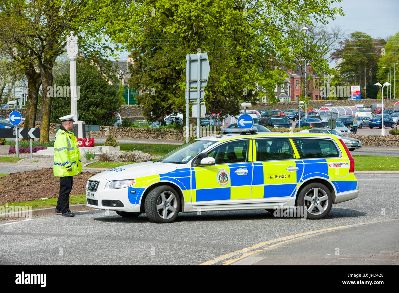 Castle Douglas, Scotland - April 25, 2011: A traffic police officer stands beside a police car that is being used as a road block. The road was closed - Stock Image