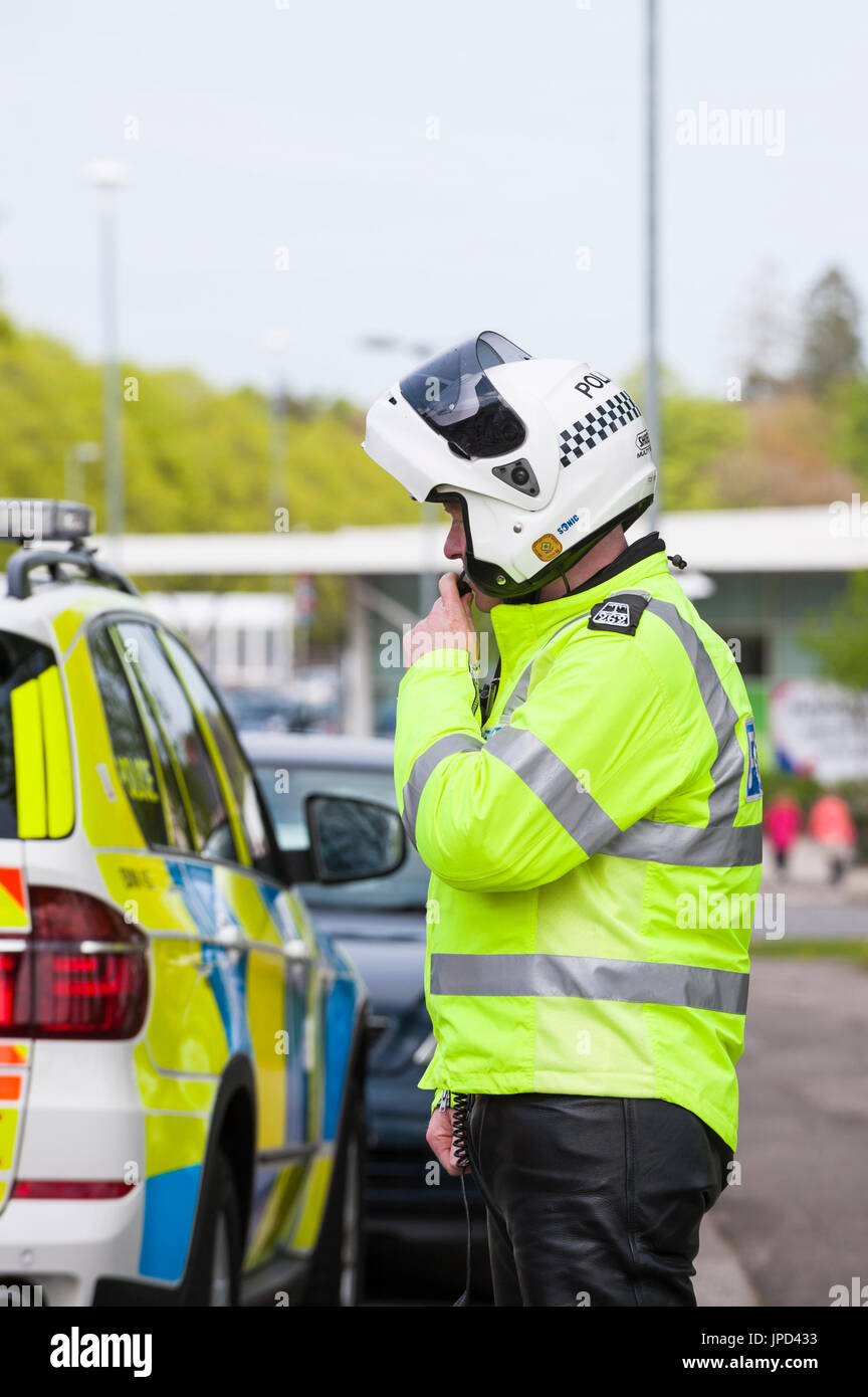 Castle Douglas, Scotland - April 25, 2011: A traffic police officer using his radio. The policeman was part of a group of police who escorted a race. - Stock Image
