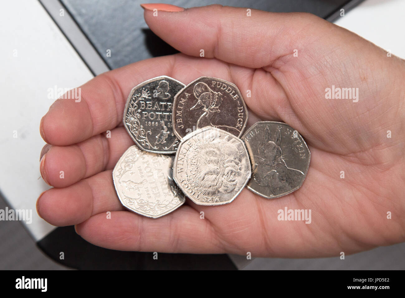 Beatrix Potter collectors British fifty pence coins in circulation jemima puddle-duck mrs tiggy-winkle squirrel nutkin in womans hand - Stock Image