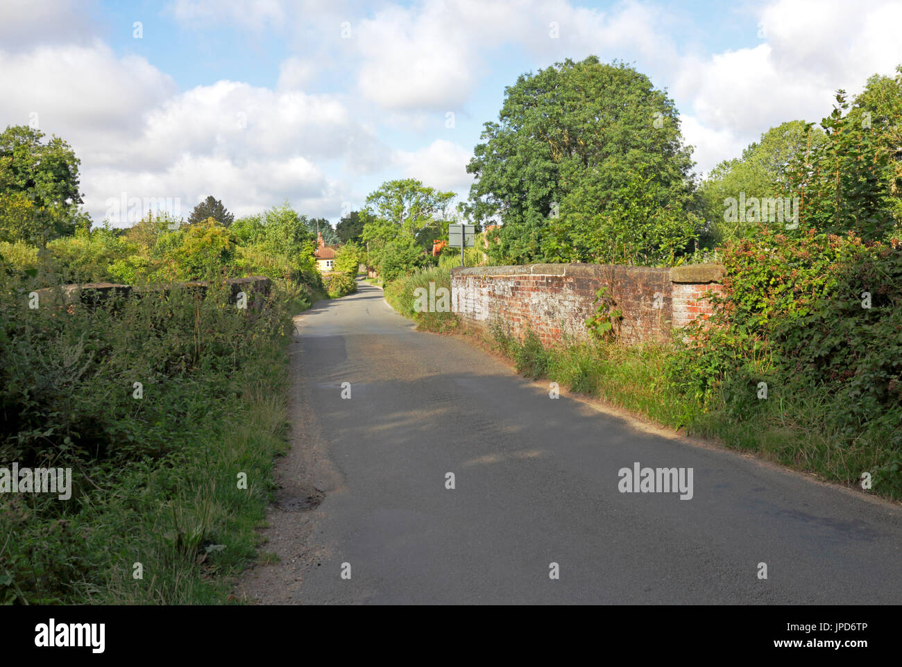 A view of a country road with old bridge over the River Ant at Briggate, near North Walsham, Norfolk, England, United Kingdom. - Stock Image