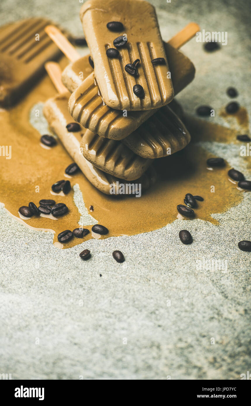 Summer healthy vegan frozen dessert. Flatlay of melting coffee latte popsicles with coffee beans over grey marble - Stock Image