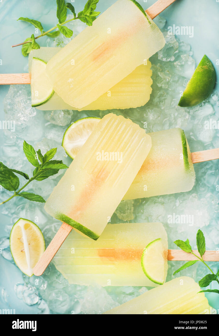 Summer lemonade popsicles with lime and chipped ice, top view - Stock Image