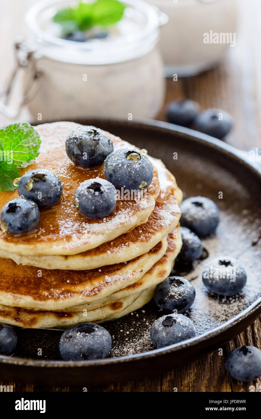 Healthy organic blueberry smoothie in glass jar and buttermilk pancakes with fresh berries on rustic wooden table - Stock Image