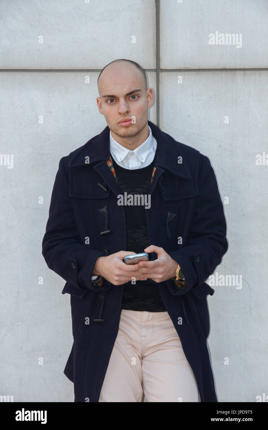 Young handsome bald businessman holding a smart phone tapping screen leaning against a white wall. - Stock Image