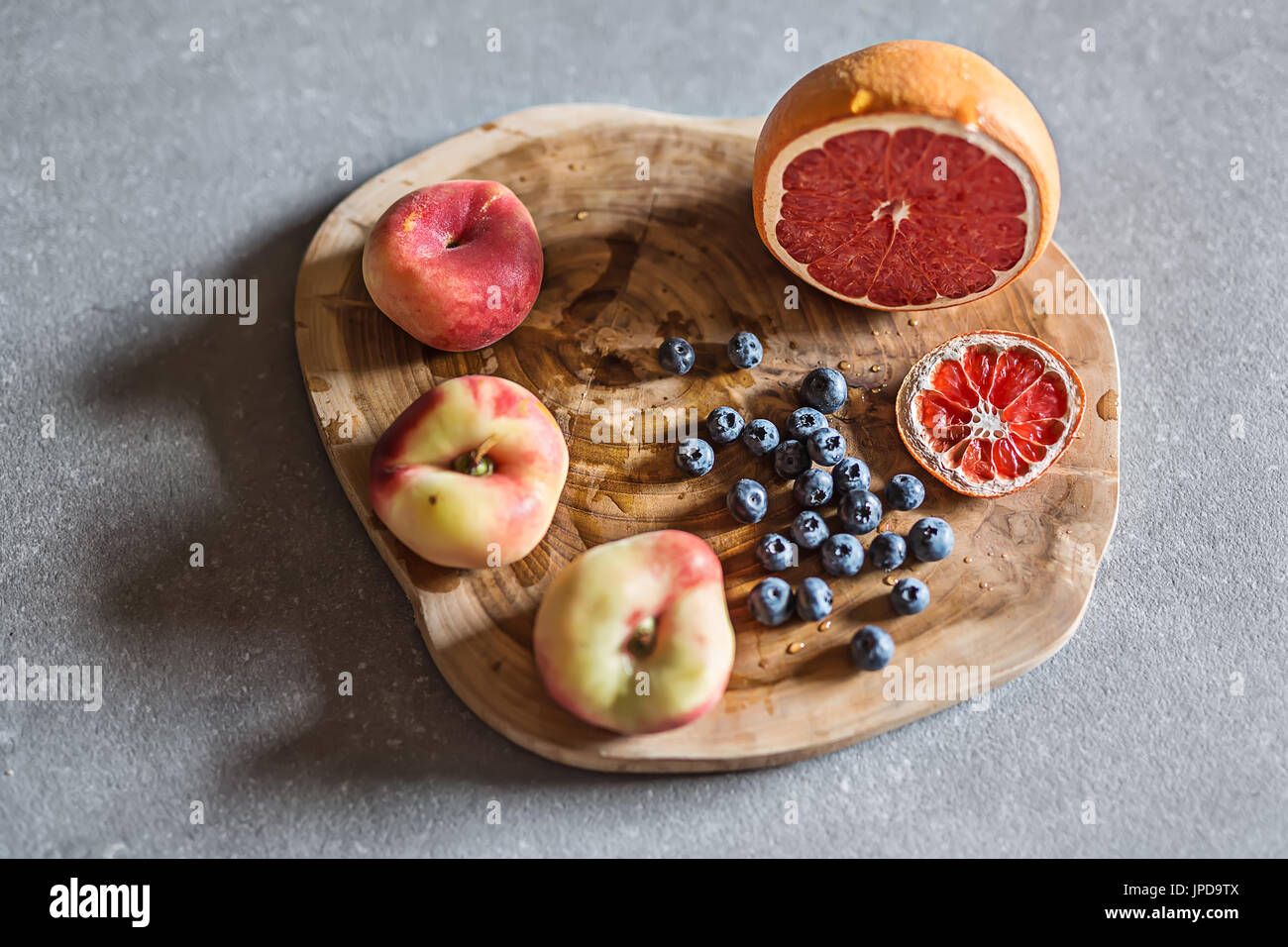 Colorful fruit on the textured wooden board on the gray surface. There is a heap of blueberries, three peaches and Stock Photo