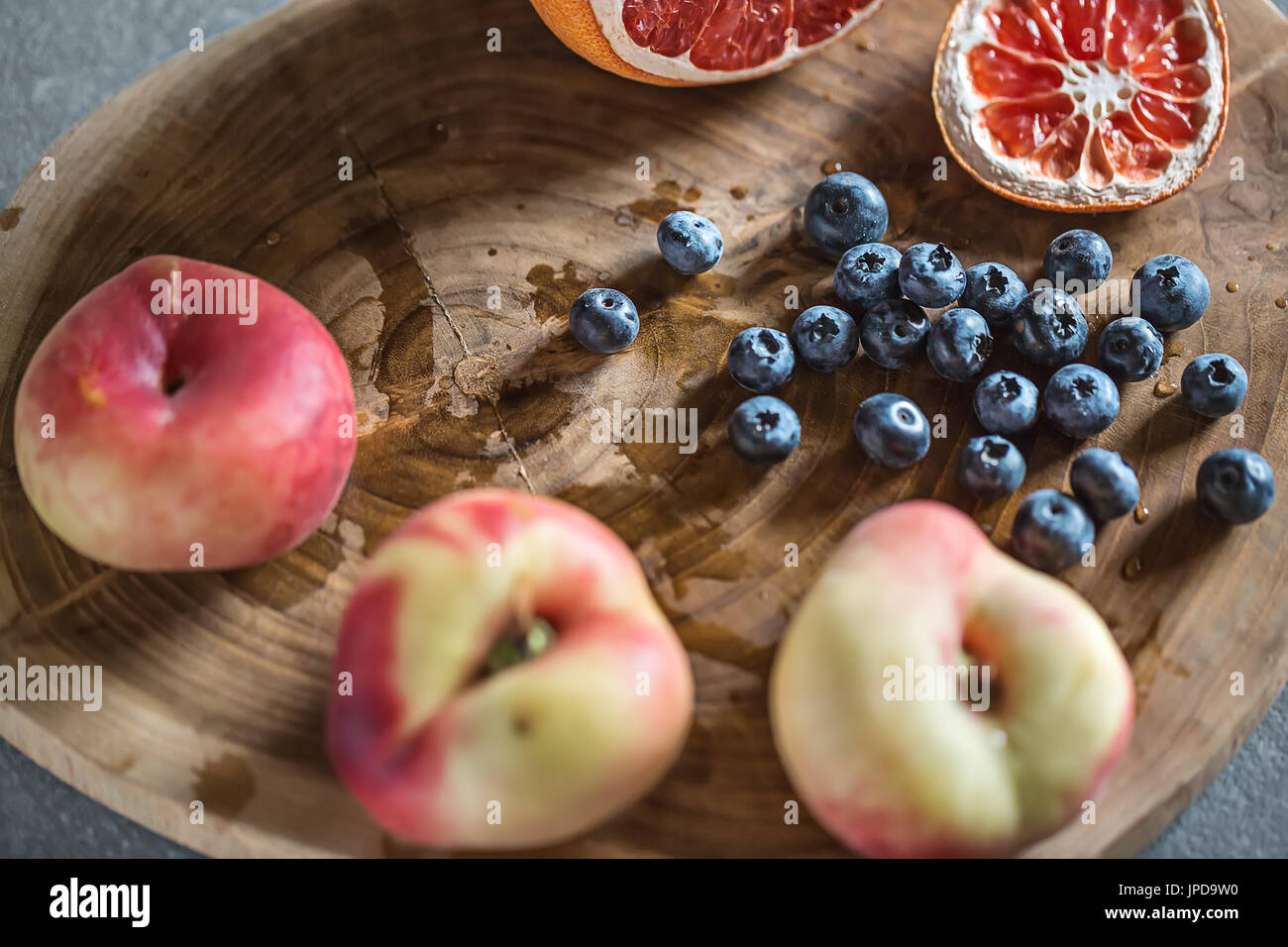 Multicolored fruit on the textured wooden board on the gray surface. There is a heap of blueberries, three peaches Stock Photo