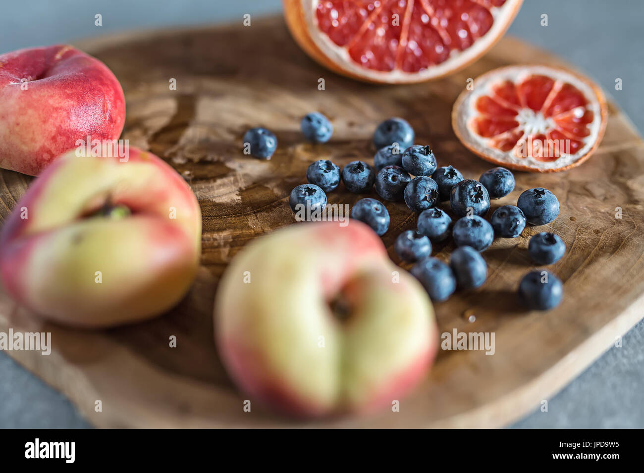 Fresh and juicy fruit on the textured wooden board on the gray surface. There is a heap of blueberries, three peaches Stock Photo