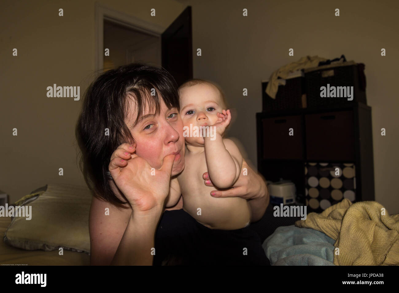mom and thumb sucking baby - Stock Image
