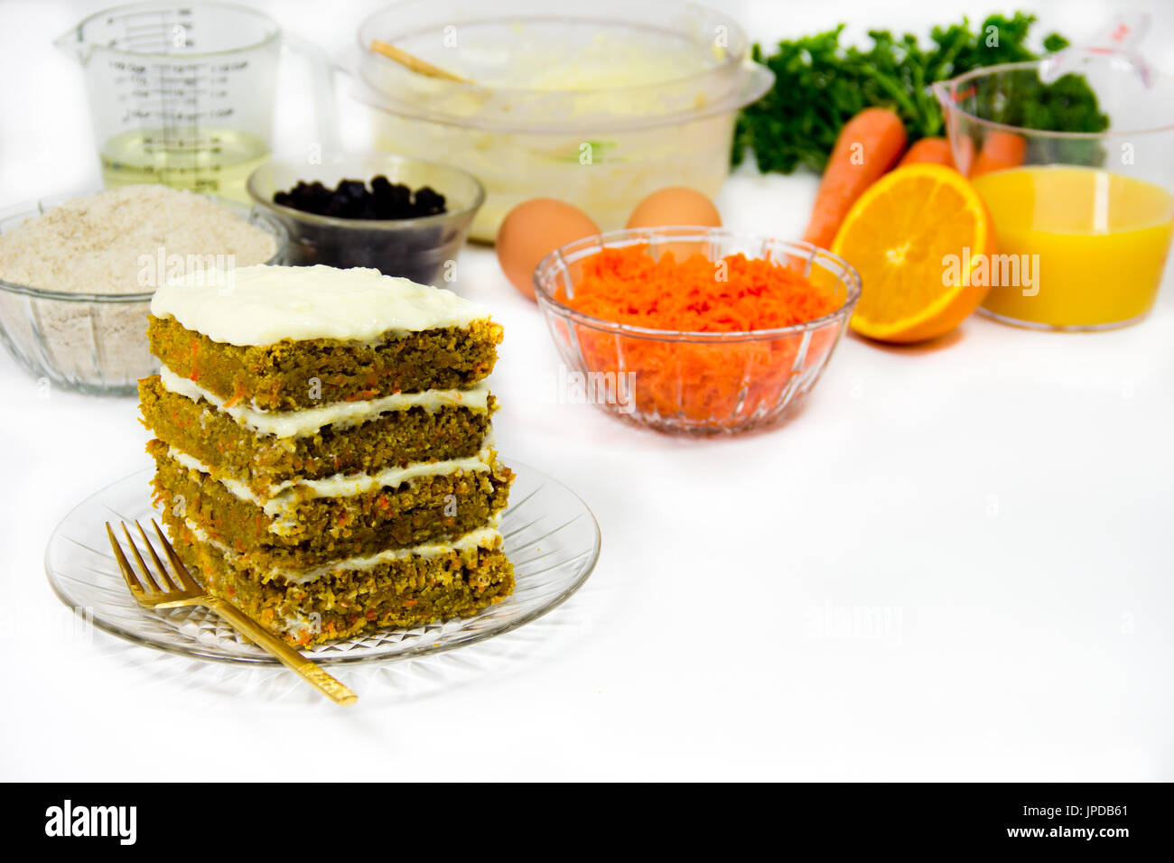 Recipe components surround a finished four-layer slice of carrot cake. - Stock Image