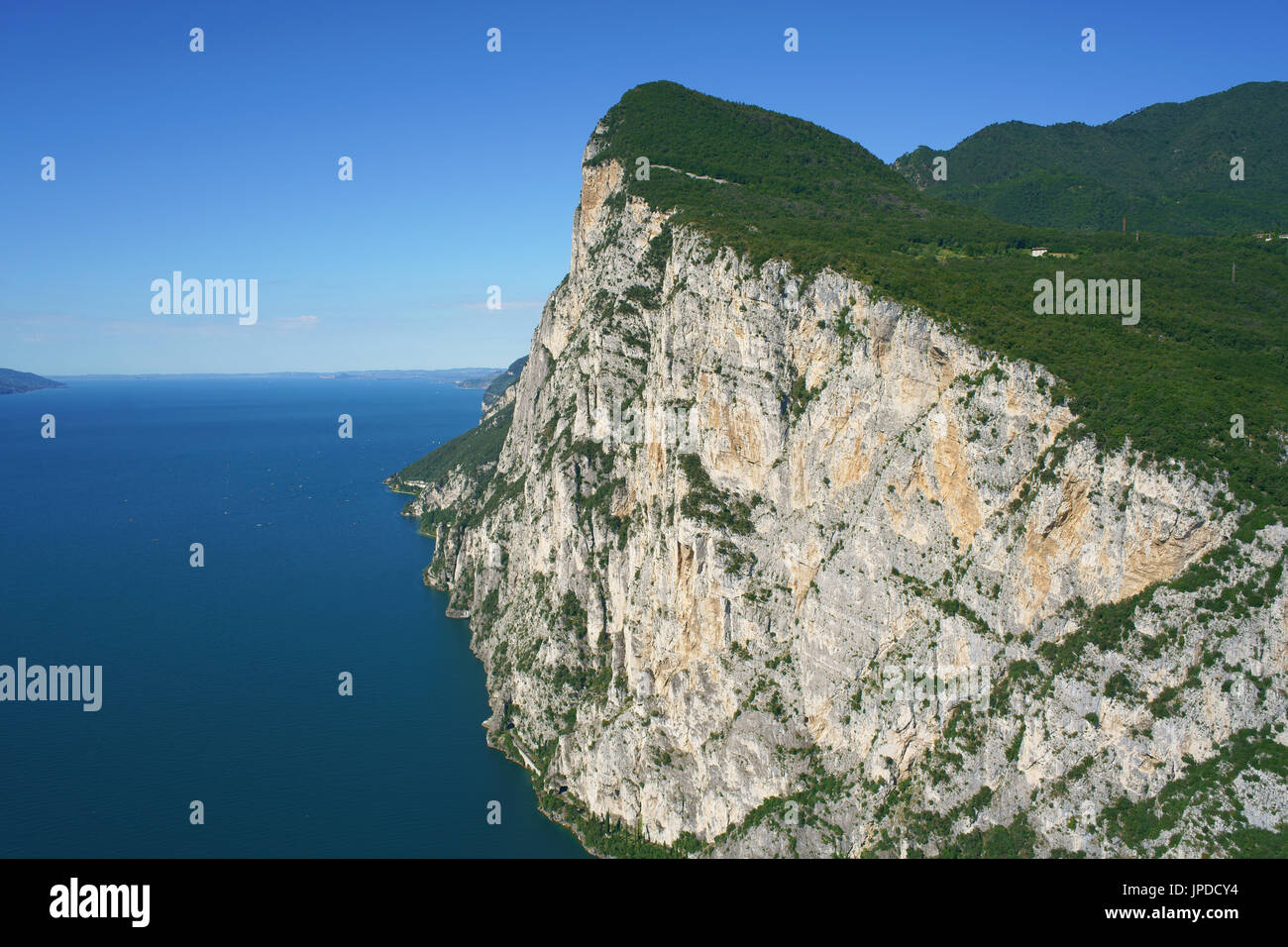 MONTE CASTELLO (779m amsl) WITH ITS GENEROUS VERTICAL DROP OVER LAKE GARDA (65m amsl) (aerial view). Tignale, Lombardy, Italy. - Stock Image