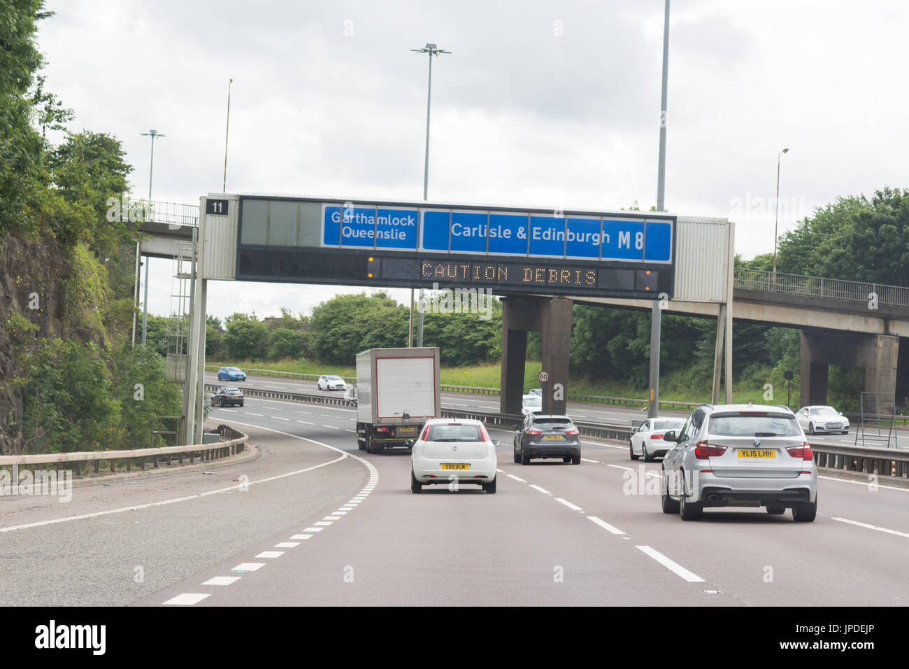 Overhead gantry sign on M8 motorway showing message 'caution debris' - Stock Image