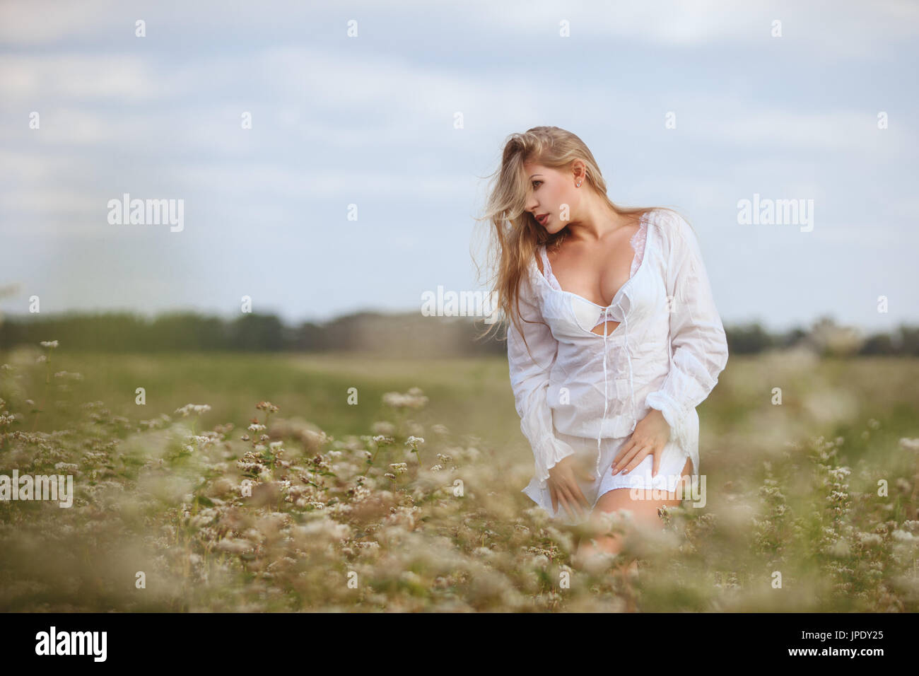 Beautiful woman in a field among the tall grass is nurtured by nature. Stock Photo