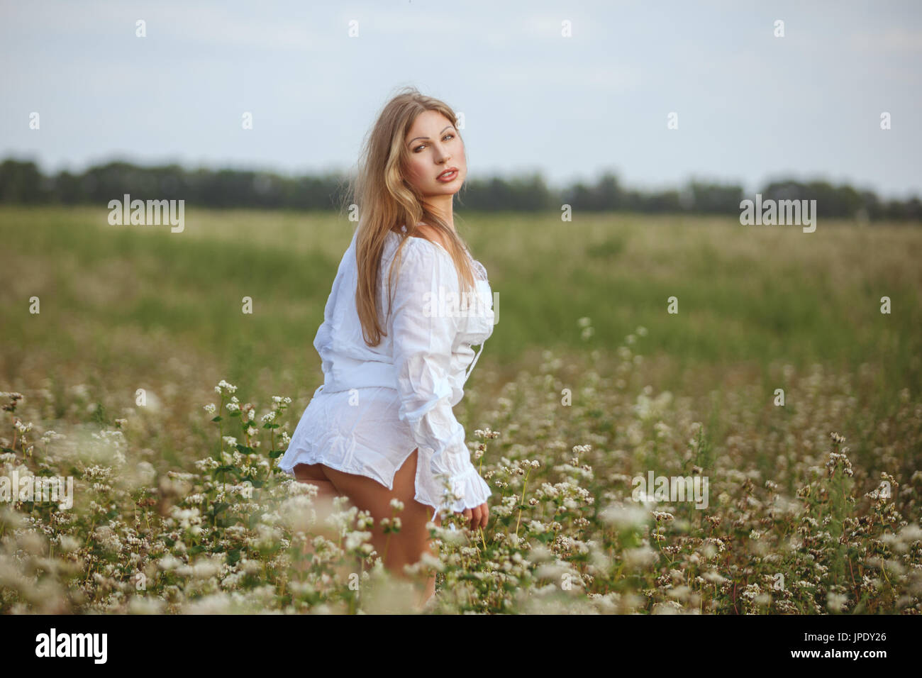 Woman in field flowers stands in the field. Stock Photo