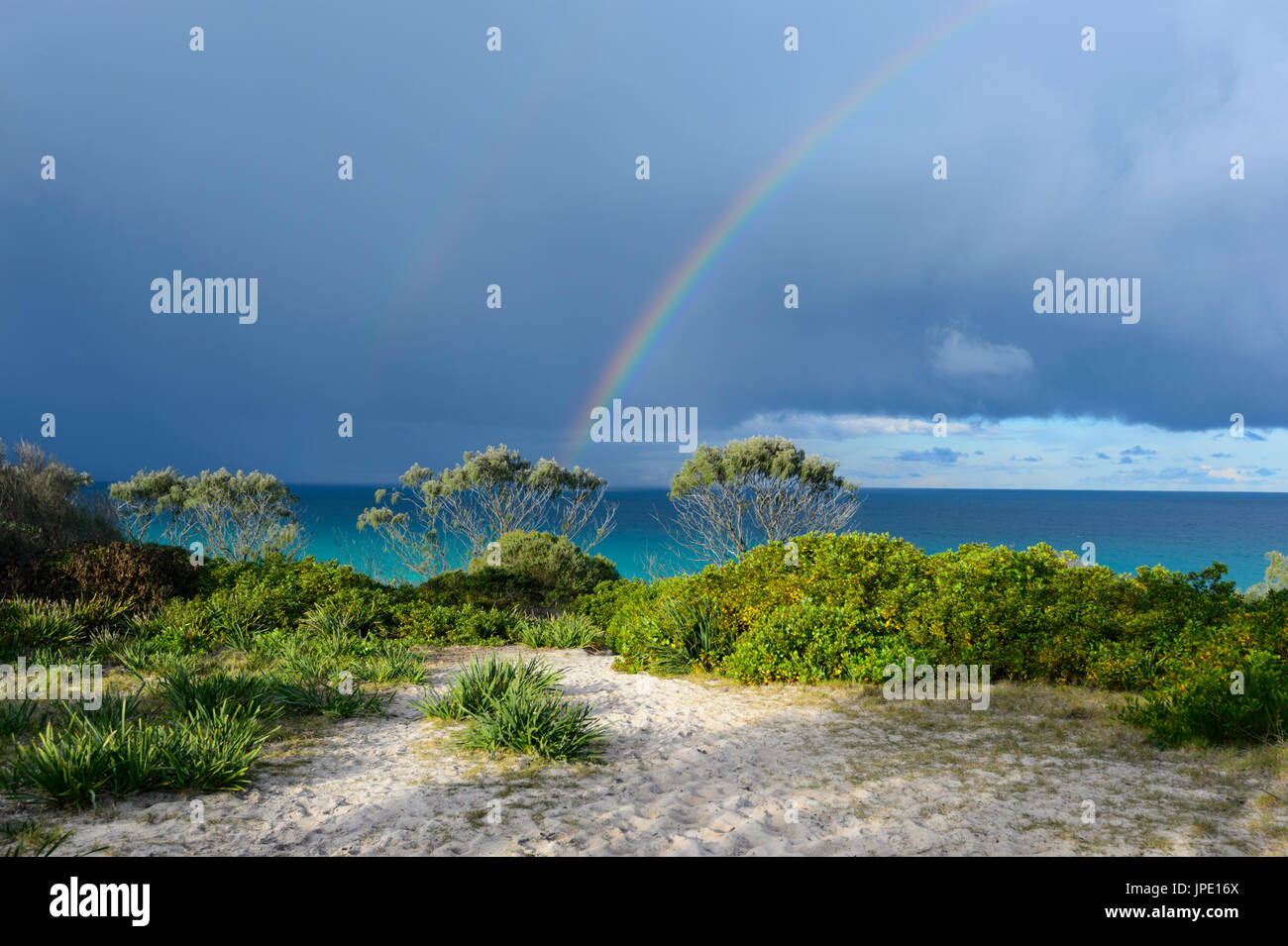 Rainbow and stormy skies over Seven Mile Beach, Forster, New South Wales, NSW, Australia - Stock Image