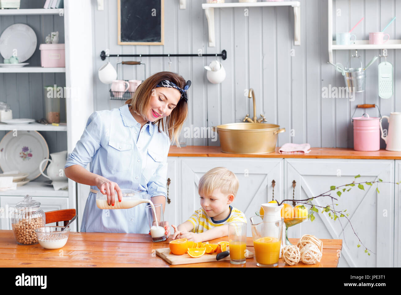 Mother and son are smiling while having a breakfast in kitchen. Mom ...