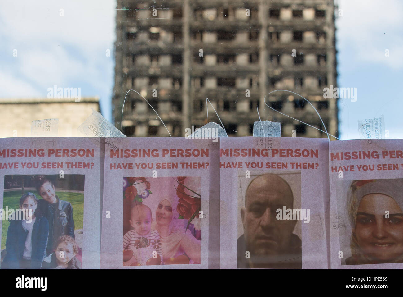 A bus stop displays posters of missing people following the devastating fire, the charred remains of Grenfell Tower can be seen in the background - Stock Image
