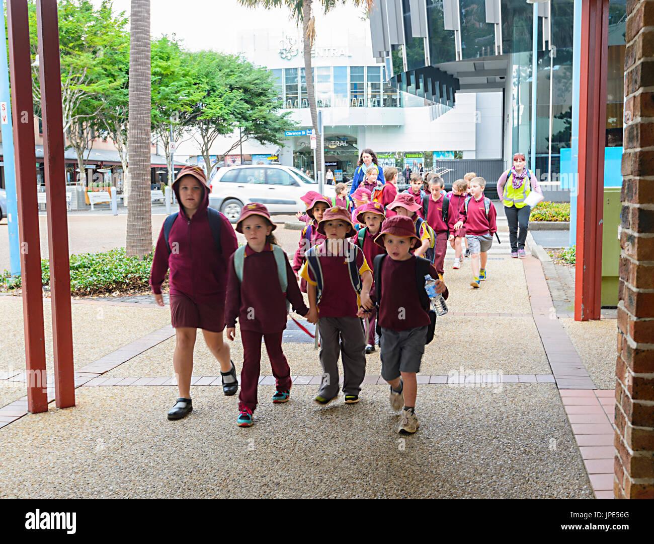 Schoolchildren wearing their school uniform walking in the street on a school day outing, Port Macquarie, New South Wales, NSW, Australia - Stock Image
