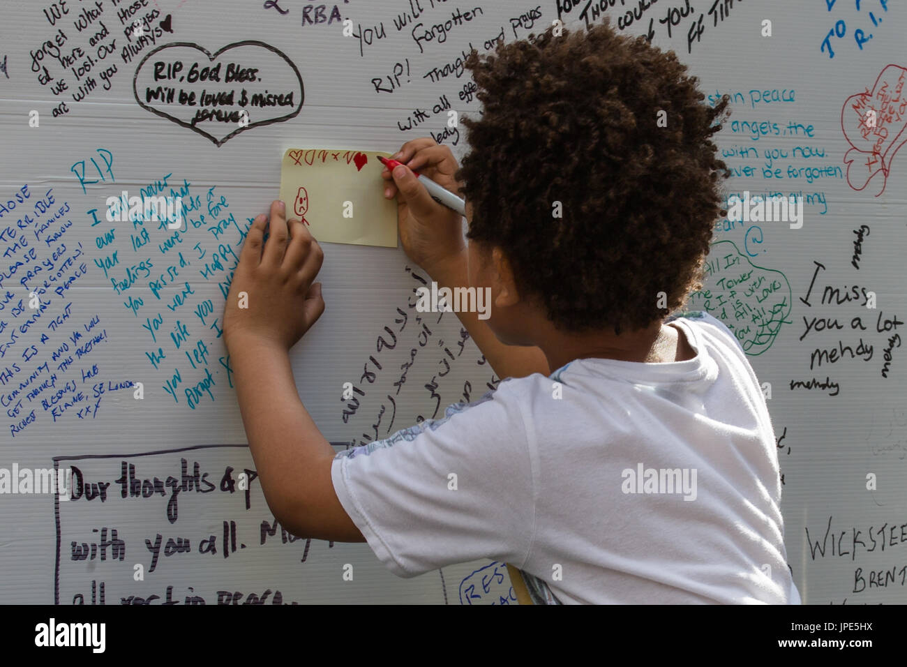 A young boy draws a message on the memorial wall for those who lost their lives in the Grenfell Tower fire. - Stock Image
