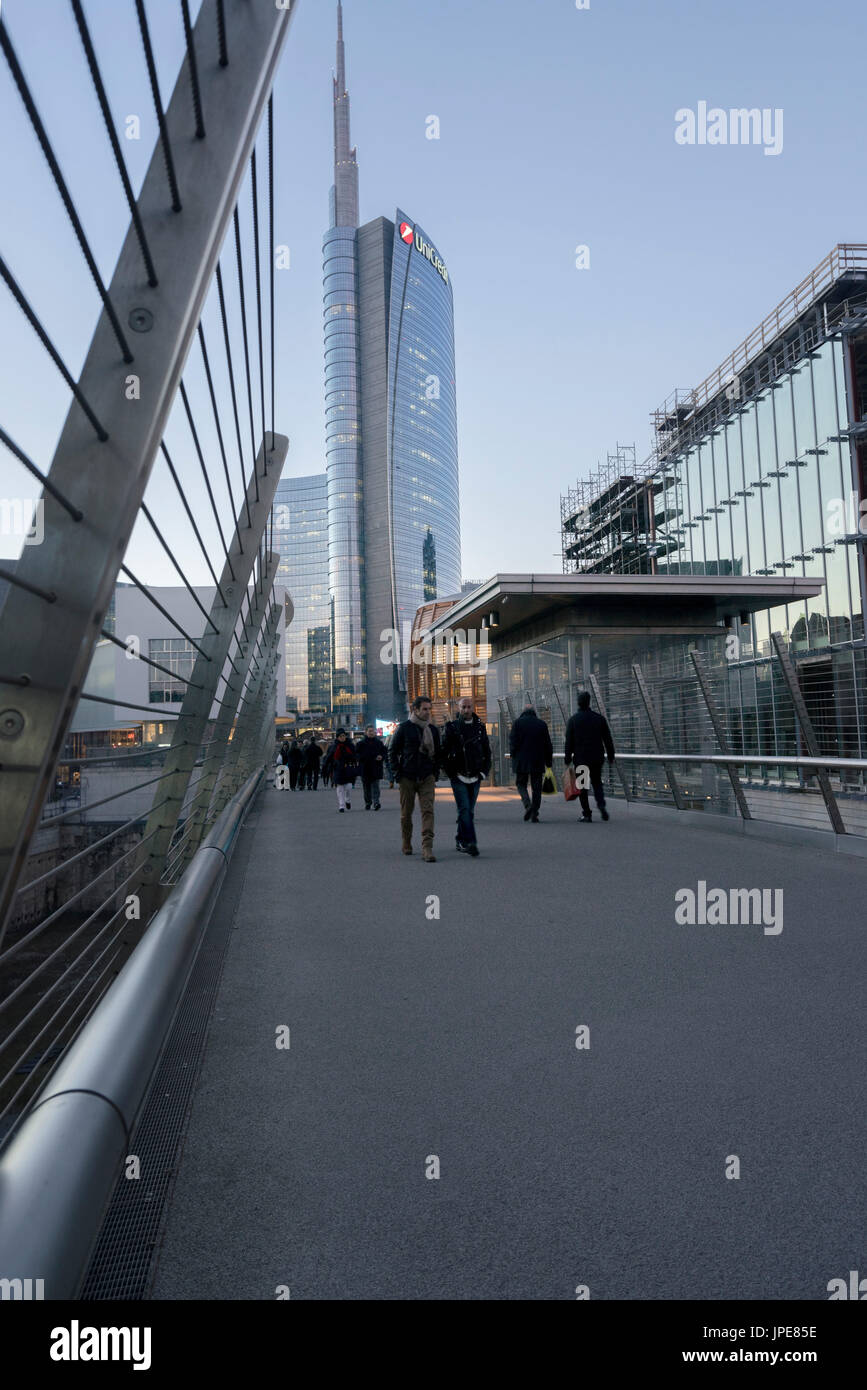 Milan, Lombardy, Italy. People walking on the bridge in front of the Unicredit Tower. - Stock Image