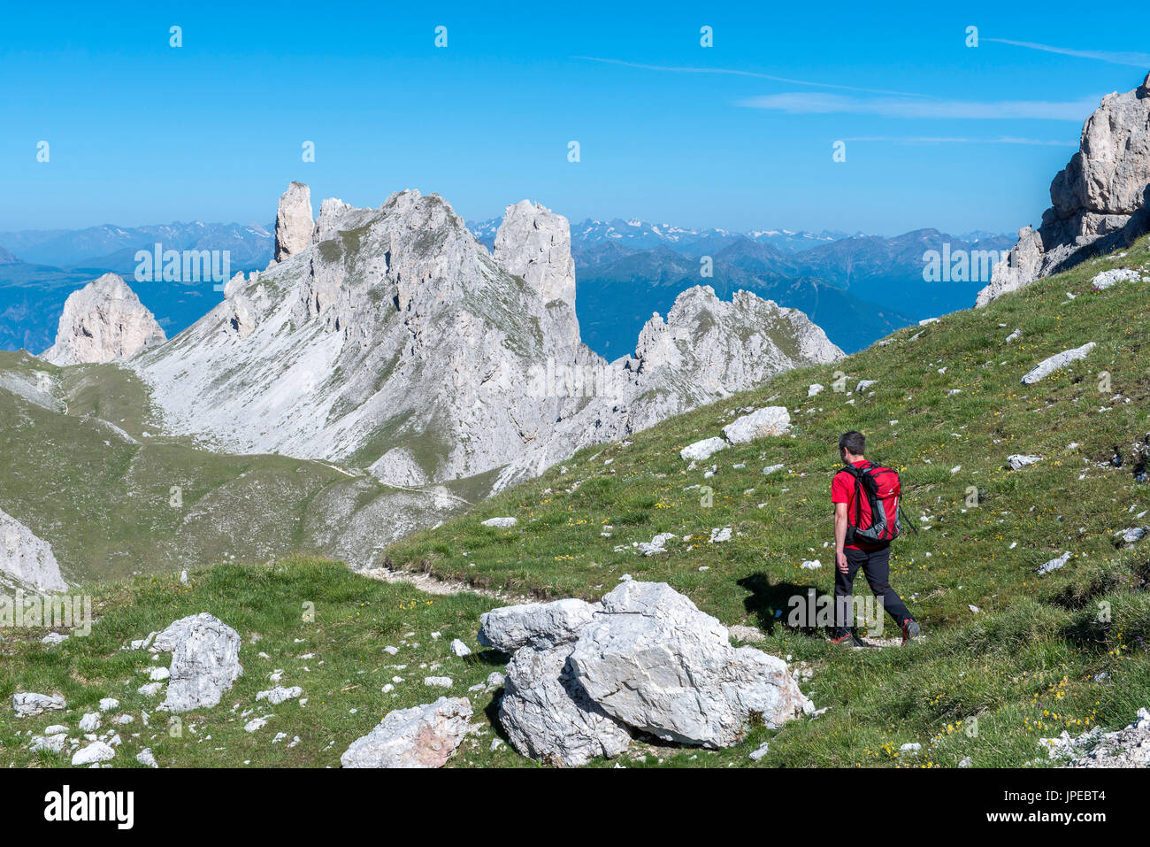 Odle di Eores, Dolomites, South Tyrol, Italy. Hiker on the Alta Via Guenther Messner. In the background the peaks of Weisslahn - Stock Image