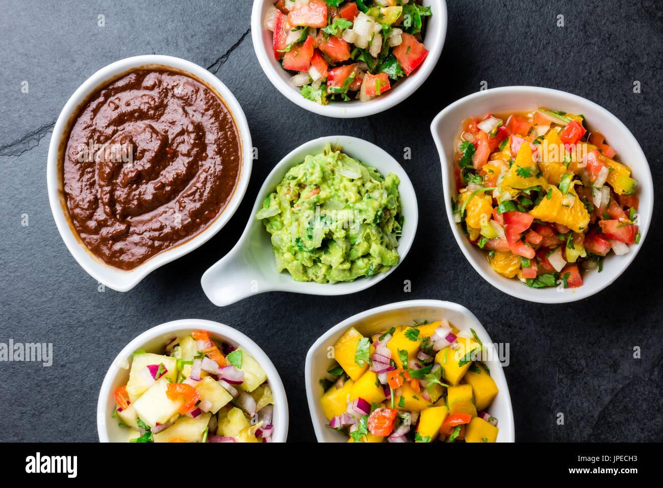 Traditional famous mexican sauces chocolate chili mole poblano, pico de gallo, avocado guacamole, salsa bandera, pinapple salsa, mango salsa on slate  Stock Photo