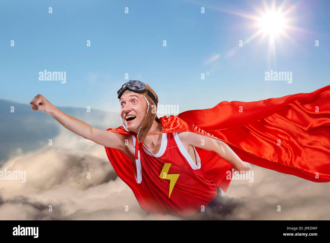 A funny super hero fly above the clouds in the sky - Stock Image