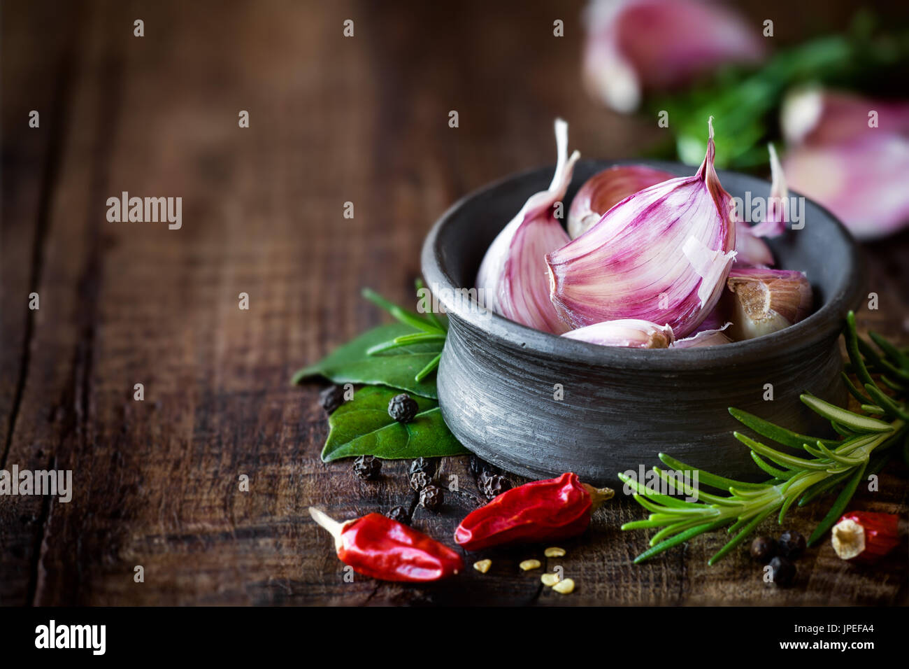 Cloves of purple garlic in a black bowl with rosemary, bay leaf, black pepper and chili pepper on dark rustic wooden - Stock Image
