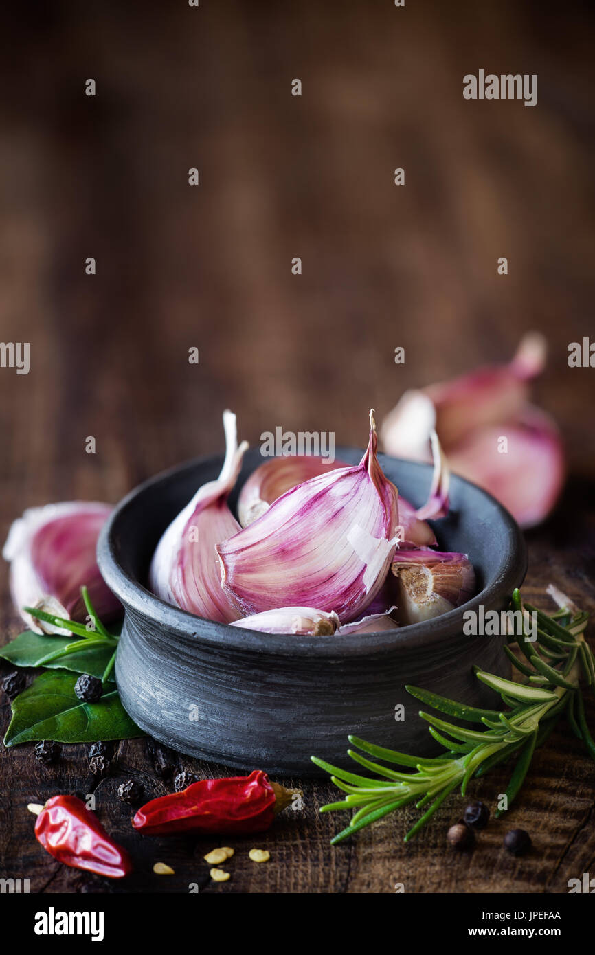 Cloves of purple carlic in a black bowl with rosemary, bay leaf, black pepper and chili pepper on dark rustic wooden - Stock Image