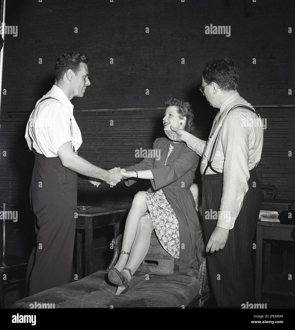 1940s, USA, New York, two actors with director, holding hands rehearsing a romantic theatre play. The attractive actress in dress, coat and heeled shoes is sitting on a beer box on top of a chaise longue. - Stock Image