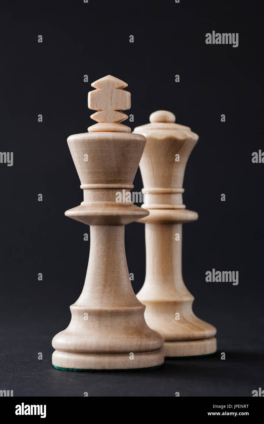 Wooden chess pieces, figures white king and queen isolated on black colored background. - Stock Image