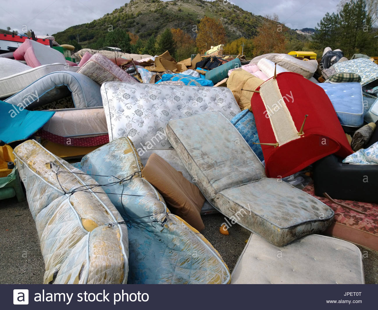 old mattress and couch piled up in an authorized recycling station - Stock Image