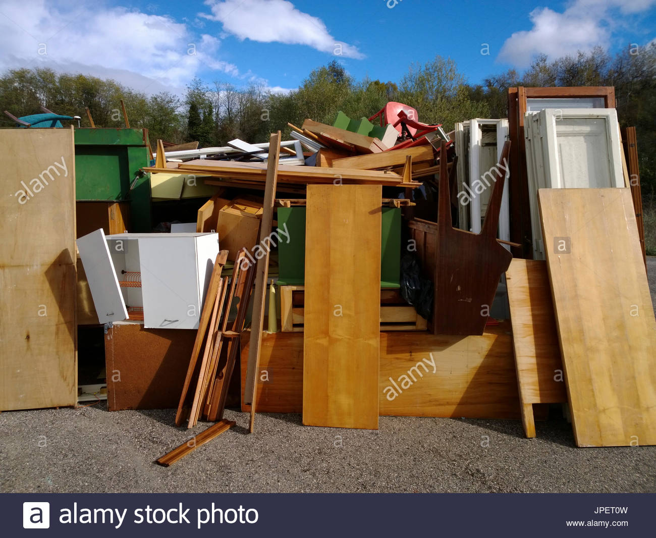 old wooden furnitures piled up in an authorized recycling station - Stock Image