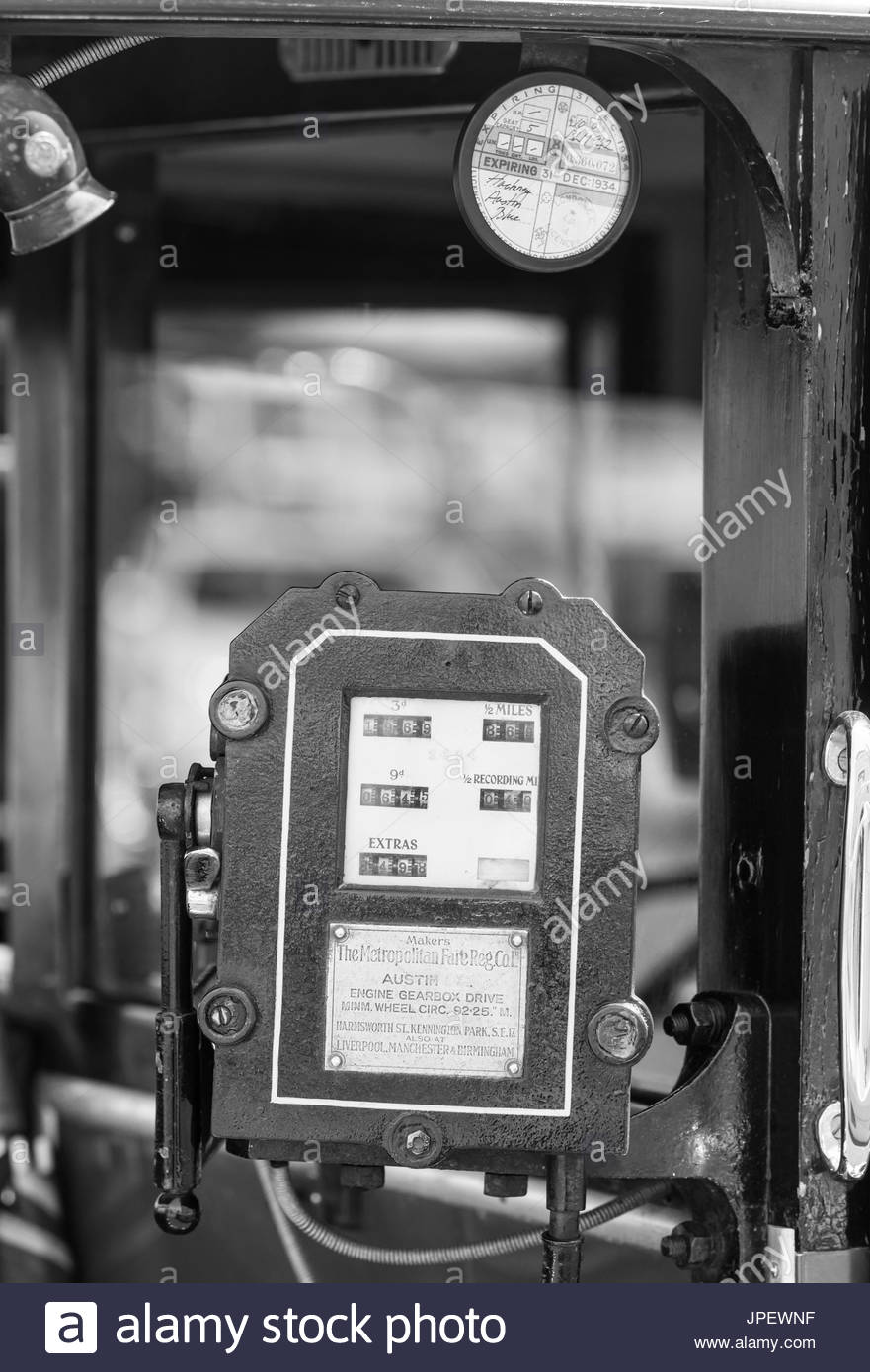 Vintage taximeter from 1930s made by The Metropolitan Fare Reg Company fitted to a vintage Austin 12/4 london taxicab. Black and white. B&W. - Stock Image