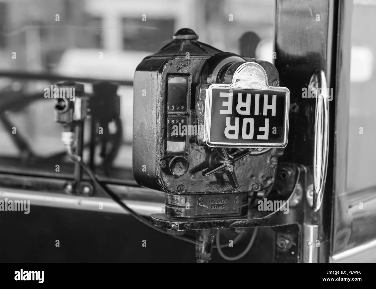 Argo Taximeter & For Hire sign from the 1930s fitted to a vintage London taxicab. Taxi fare meter fitted to vantage Austin Six taxi in the UK. B&W. - Stock Image