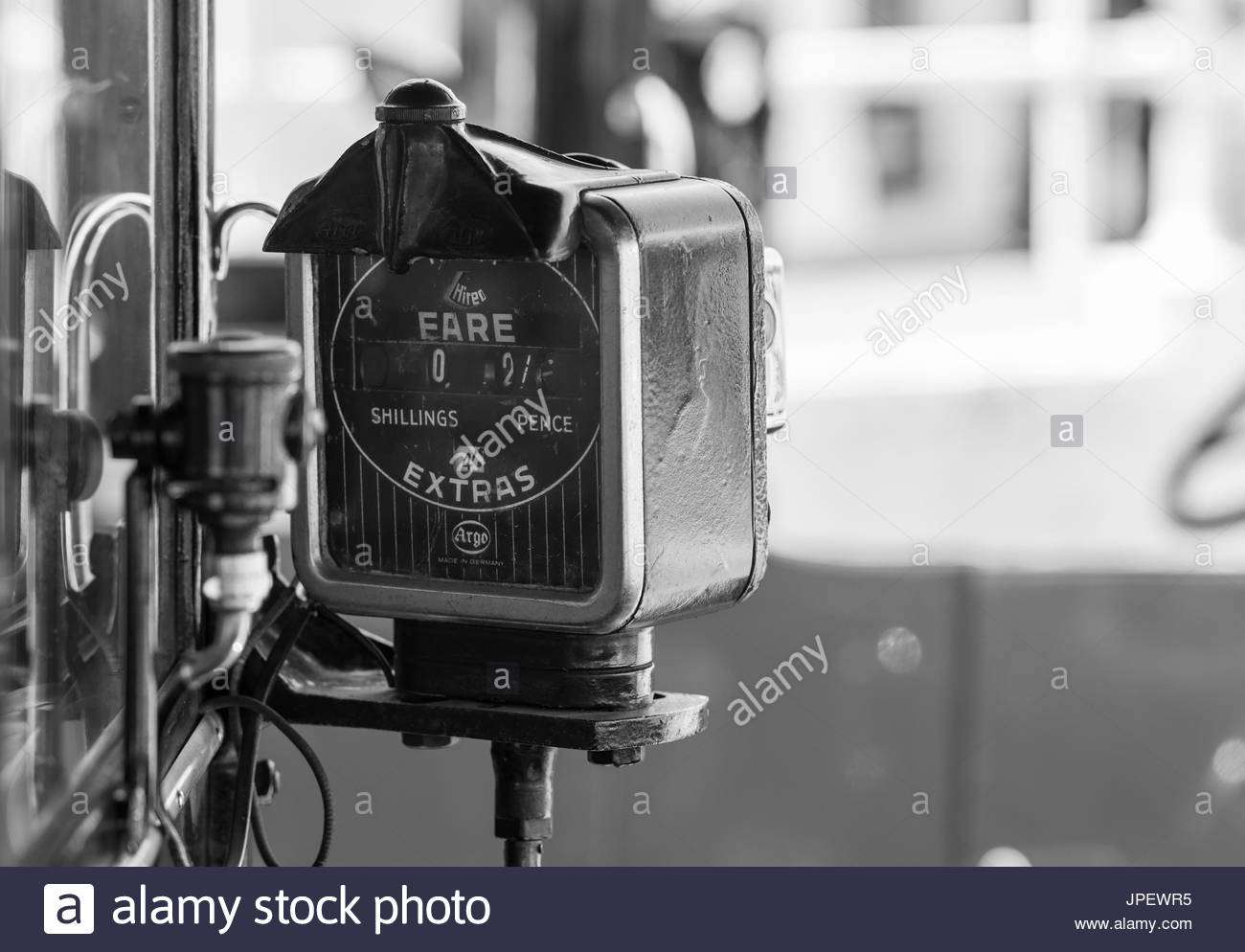 Argo Taximeter from the 1930s fitted to a vintage London taxicab. Taxi fare meter fitted to a vantage Austin Six taxi cab in the UK. Black and white. - Stock Image