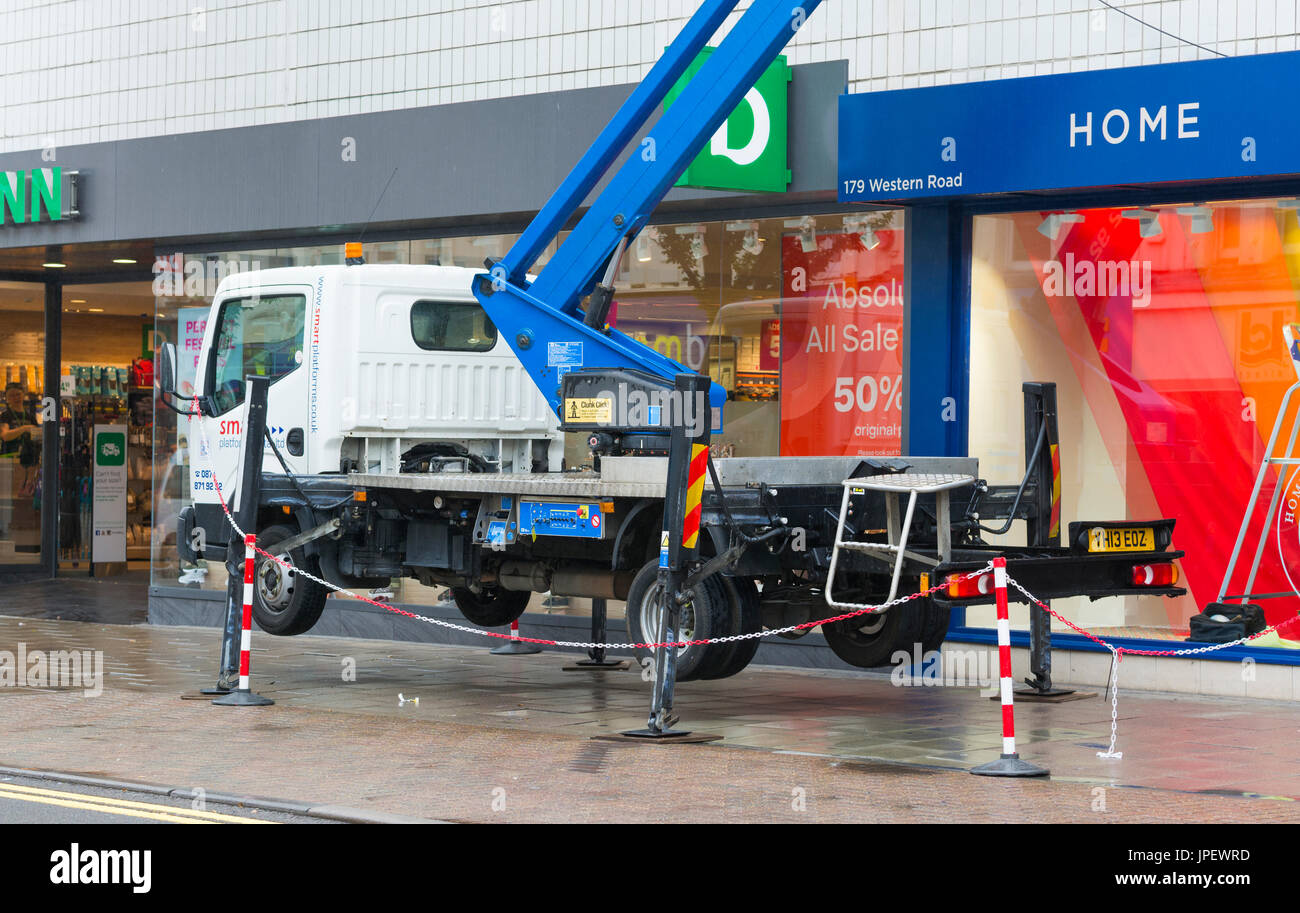 Mobile cherry picker crane platform truck being supported off the ground with struts. - Stock Image