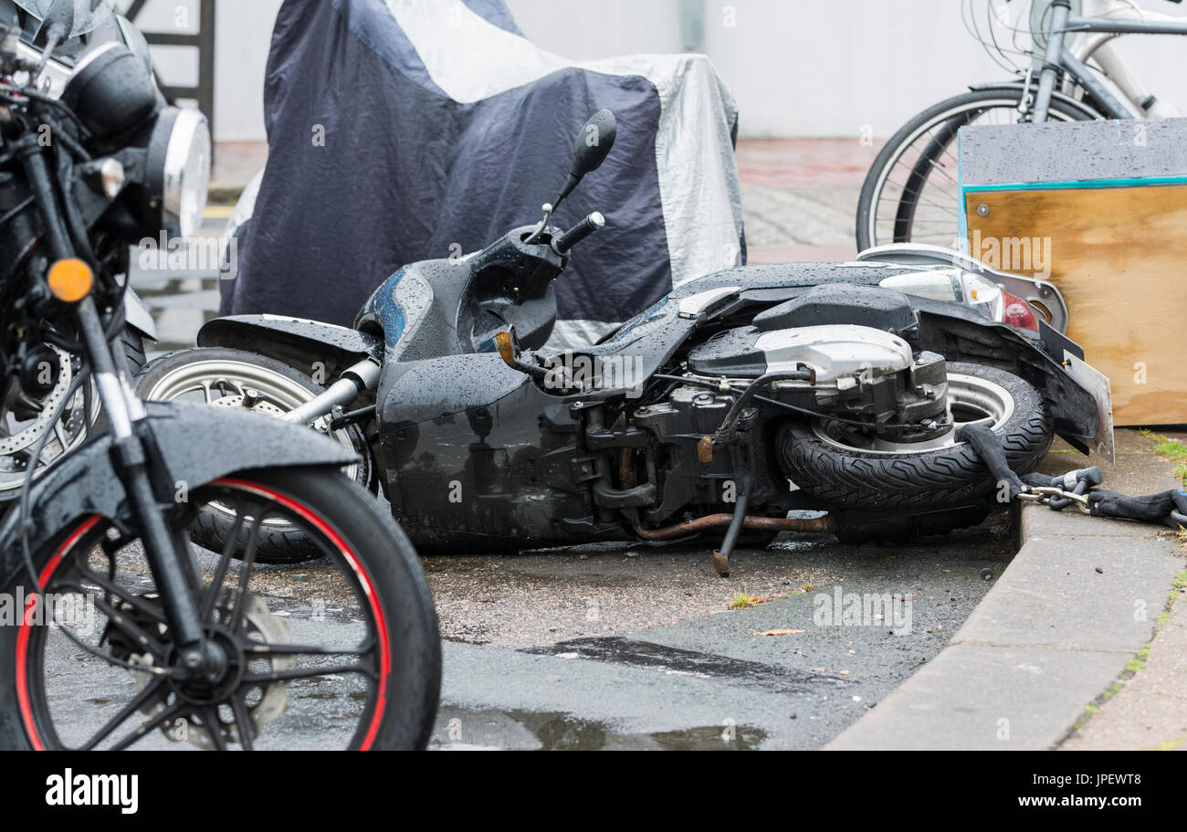 Motorcycle parked with others and fallen over onto the ground. - Stock Image