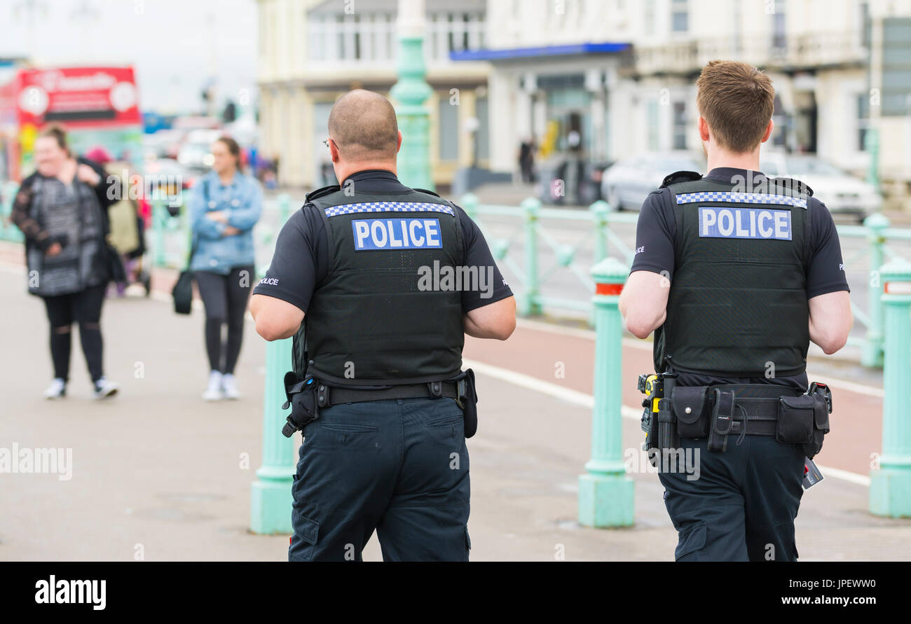 Pair of uniformed Sussex Police officers on the promenade in Brighton, East Sussex, England, UK. - Stock Image