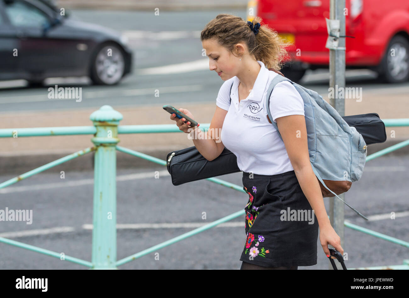 Young woman walking along looking at mobile phone. Online culture. Modern life concept. Always connected. - Stock Image